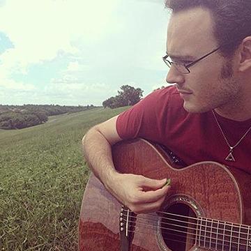 Jonathan, holding a guitar, overlooking grassy hills.